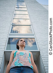 Pretty woman standing in front of a tall building