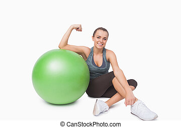 Young woman showing her arm muscles sitting next to a...