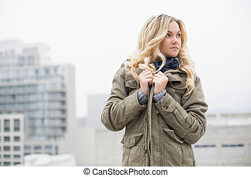 Gorgeous trendy blonde posing outdoors on urban background