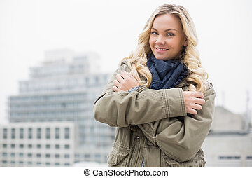 Cold trendy blonde posing outdoors on urban background