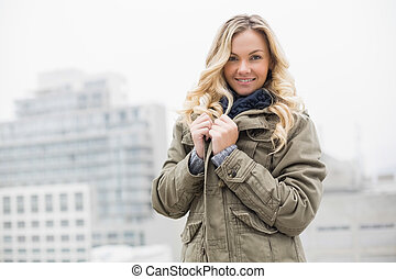 Happy trendy blonde posing outdoors on urban background