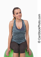 Attractive fit woman sitting on fitness ball looking at...