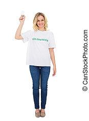 Happy blonde volunteer holding light bulb on white...