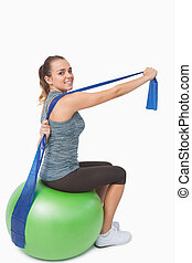Cheerful woman stretching her arms using a resistance band