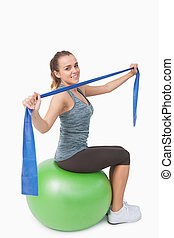 Attractive young woman sitting on therapy ball stretching...