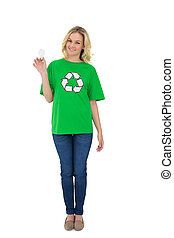 Smiling cute environmental activist holding light bulb on...