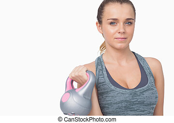 Young woman training her arms with a kettle bell