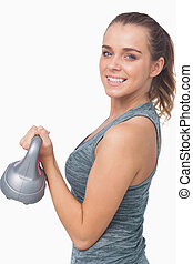 Happy woman training with a kettle bell on white background