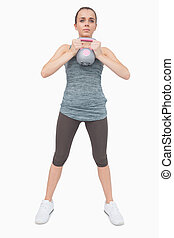 Cute woman training her body with a kettle bell