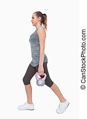 Sporty woman training her body walking with a kettle bell