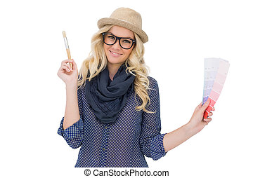 Cheerful trendy blonde with classy glasses holding color...