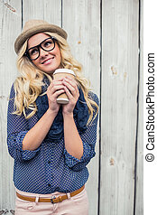 Happy fashionable blonde holding coffee outdoors on wooden...