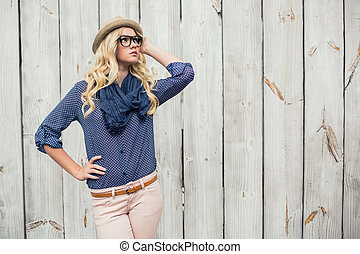 Day dreaming trendy model posing on wooden background