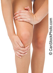 Close up of slim woman touching her injured knee on white...