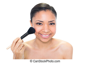 Delighted young dark haired model applying powder on her...