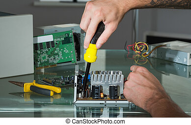 Hands repairing hardware with screw driver in bright office