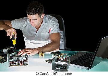 Handsome stern computer engineer working by night with screw driver at his lit desk