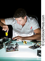 Handsome computer engineer working by night with screw driver