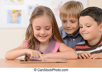 Children with digital tablet. Cheerful children looking at...