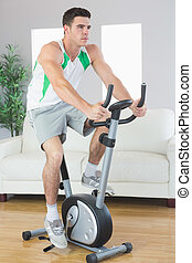 Determined handsome man training on exercise bike in bright...