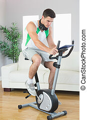 Handsome man training on exercise bike using tablet in...