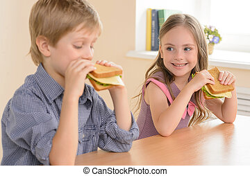 Children eating sandwiches. Two cheerful children eating...