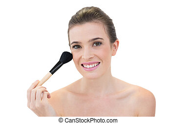 Cheerful natural brown haired model applying powder on her...
