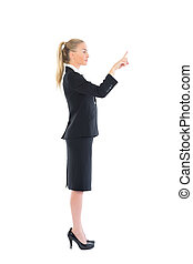Profile view of young business woman pointing on white...