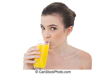 Lovely natural brown haired model drinking orange juice on...