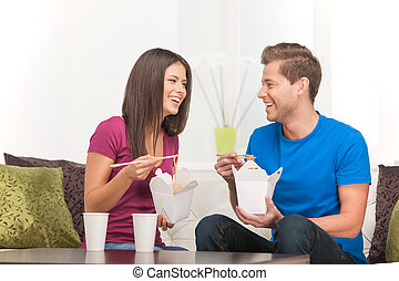 Eating Asian food. Beautiful couple eating Asian food from...