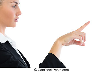 Profile view of attractive businesswoman pointing on white...