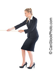 Focused blonde businesswoman pulling a rope on white...