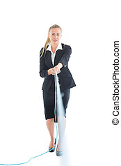 Focused blonde businesswoman using a hose looking at camera