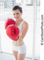 Motivated fit brown haired model in sportswear wearing red...
