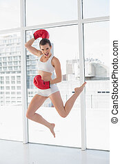 Motivated fit brown haired model in sportswear jumping in...