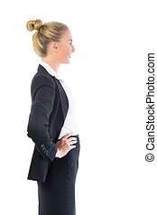 Profile view of cheerful young businesswoman posing with...