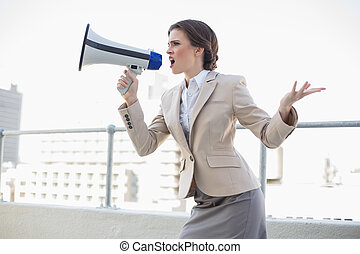 Furious stylish brown haired businesswoman shouting in a...