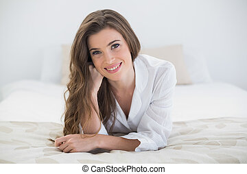 Pleased casual brown haired woman in white pajamas lying on...