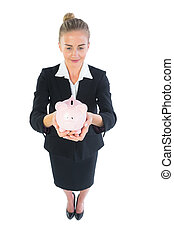 High angle view of modern businesswoman showing a piggy bank