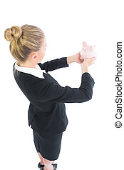 Side view of blonde businesswoman holding a piggy bank