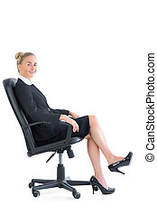 Gorgeous chic businesswoman sitting on an office chair...