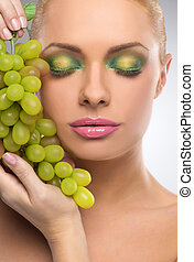 Beauty with grape. Portrait of beautiful women with make-up holding grape while isolated on grey