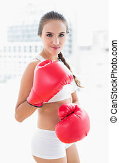 Sporty brunette woman wearing red boxing gloves in bright...