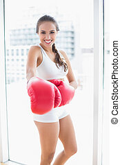 Cheerful sporty brunette wearing red boxing gloves in bright...