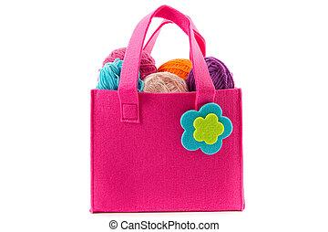 balls of yarn in a felt handbag