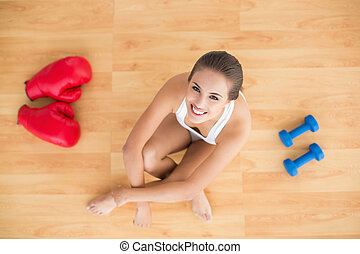 Sporty brunette woman sitting next to red boxing gloves and...