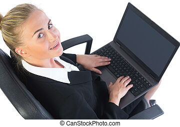 Cute businesswoman using her notebook sitting on an office...
