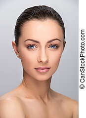 Beautiful make-up. Portrait of beautiful women with make-up looking at camera while isolated on grey