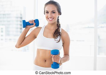 Smiling young brunette holding dumbbells in bright room