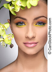 Beautiful make-up. Portrait of beautiful young women with make-up looking at camera while isolated on grey